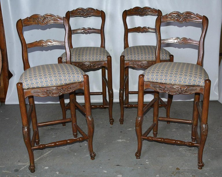 Set of 4 Louis XV French provincial country style bar or kitchen counter stools. Stools feature solid carved wood frames, upholstered inset seat cushions, ladder backs and cabriole legs. Seat height - 27