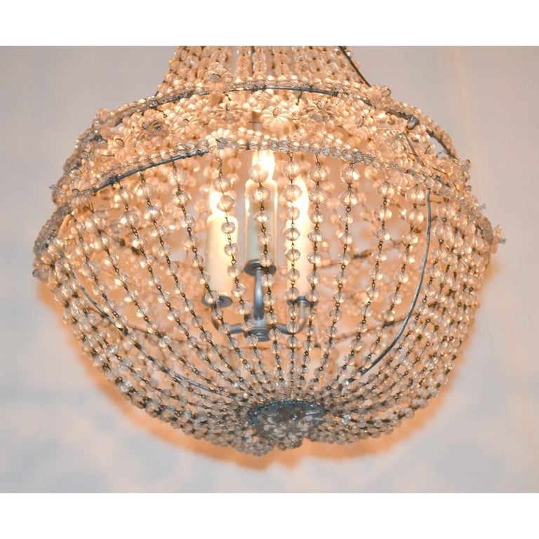 Lovely French crystal basket chandelier. The top with cascades of bead crystals leading to a central band accented with crystal rosettes. The basket-form base draped with multiple strands of bead cut crystals,  circa 1920.