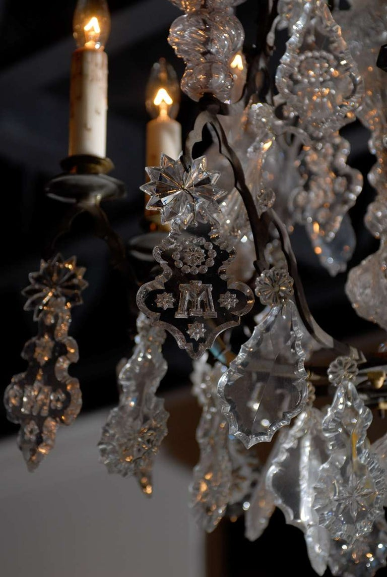 A French Baroque Revival crystal six-light chandelier from the mid 19th century, with black patinated bronze armature, pendeloques, rosettes and monograms. Found in a French church, this exquisite crystal nine-arm chandelier features a central