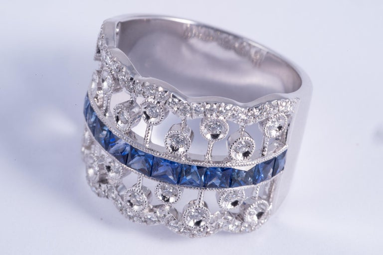 This very beautiful ring features french cut blue sapphires. The sapphires weigh 1.46cts total. The accent diamonds have G-H color and SI1 clarity. The ring is set in 14k white gold. the gold weighs 7.80grams. It is a size 6.75 and can be sized.