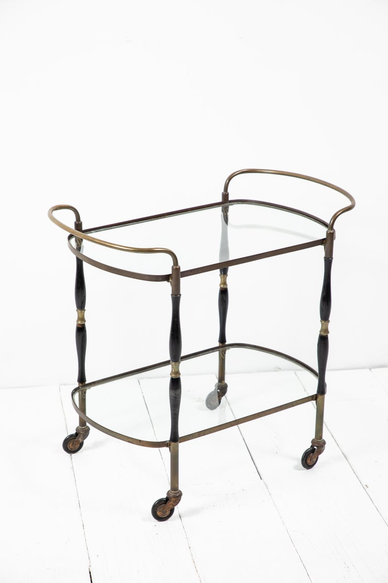 Beautiful deco bar cart with black and brass turned legs with two glass shelves. The bar cart sits on wheels.