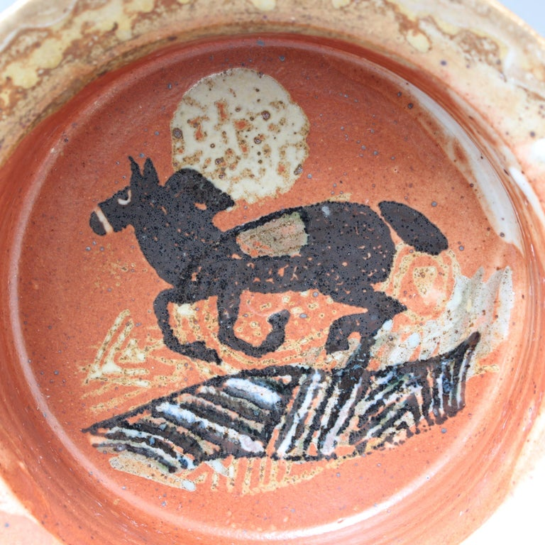 French decorative ceramic bowl (circa 1950s). Discovered in the South of France, this is a diminutive but elegantly stylish bowl of buff-colored earthenware glaze, covered similarly on the inside with a galloping horse under-the-moon motif. The lip