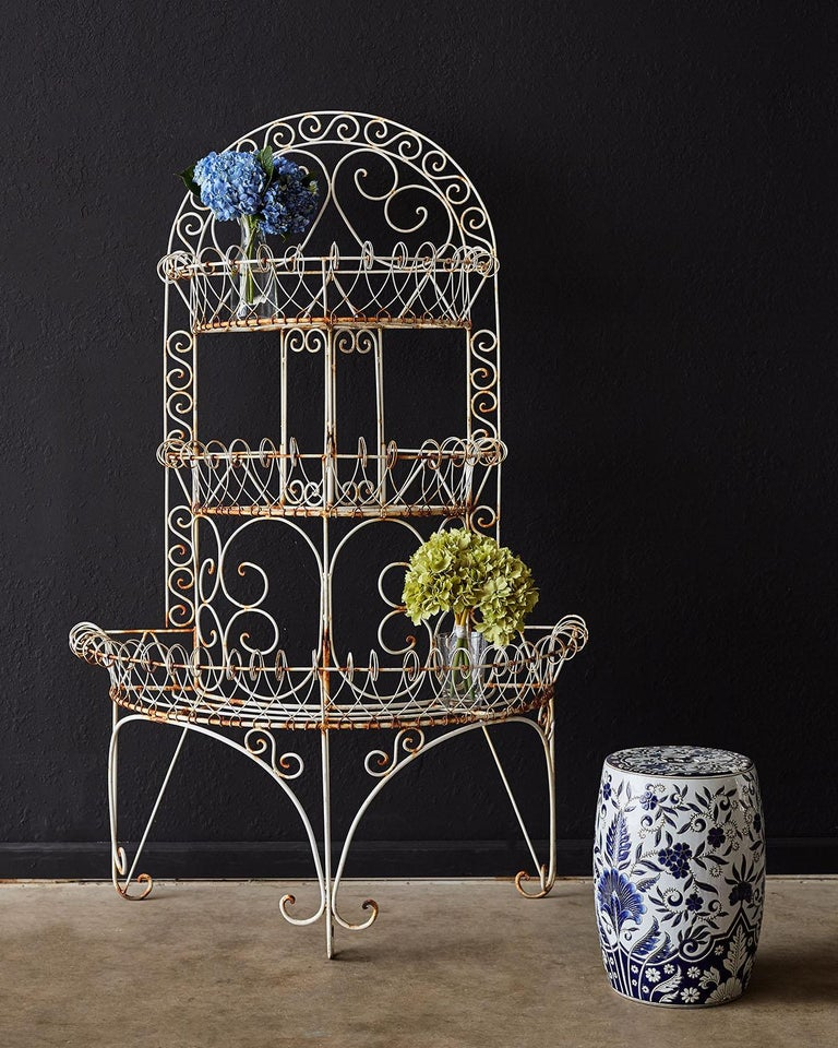 Grand French three-tier iron and wire plant stand having a demilune form. The three tier iron frame is decorated with wire bent in a graceful scrolled border on each shelf. Supported by three sets of legs ending with scrolled feet. Excellent joinery