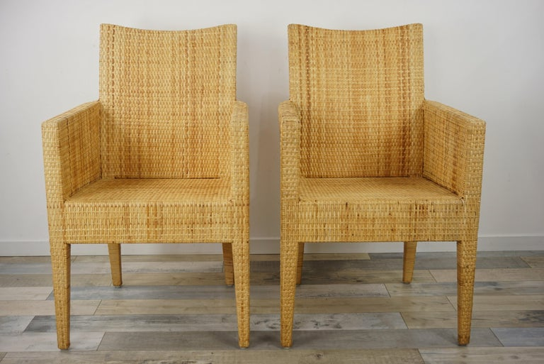 Sculptural bridge armchairs with a structure in solid wood covered with a braiding of natural rattan blade.