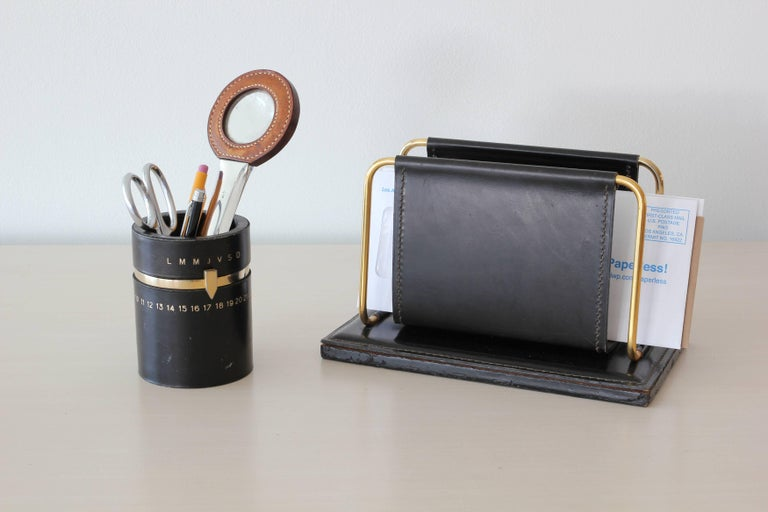 French black leather desk accessory in the style of Jacques Adnet.  Fantastic pencil holder with days of the week and month in brass.
