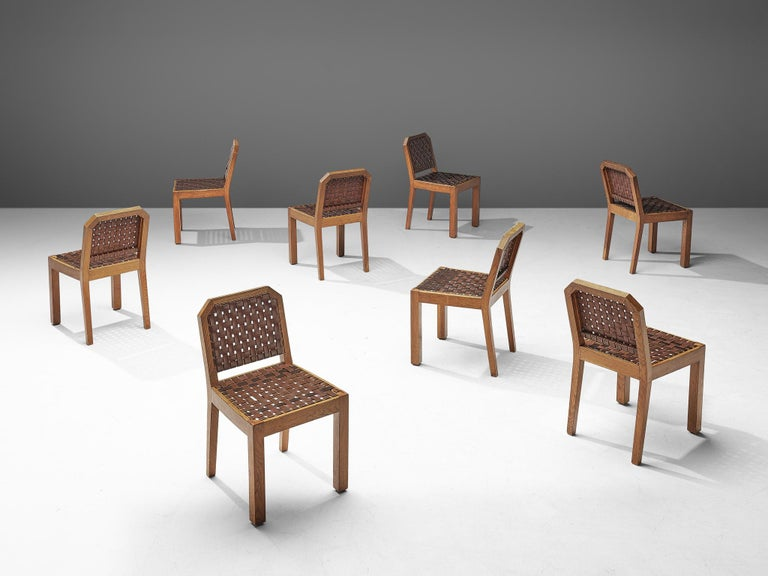 Set of 8 dining chairs, oak and leather, France, 1940s  This set of 8 French dining chairs has a sturdy design, with strong proportions. The frame consists of bulky lines of which the front legs are straight and thick, while the hinge legs are