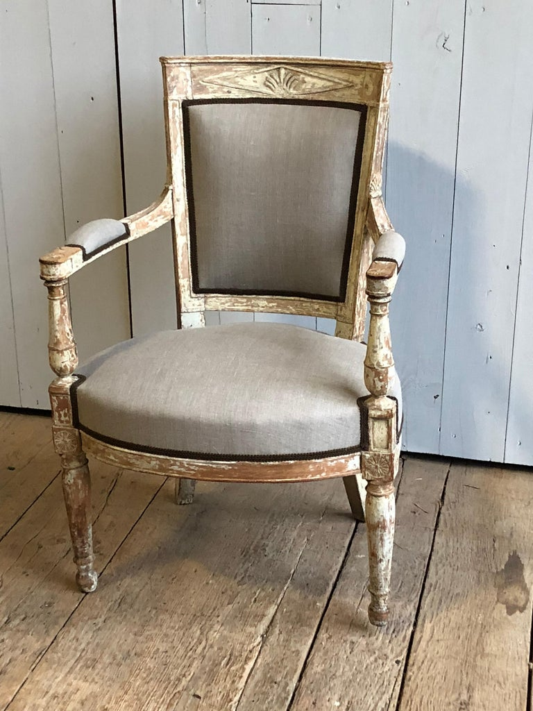 "A French neoclassic Fauteuil, Directoire period, circa 1800 with newly upholstered seat and back in grey linen and brown gimp. Original painted finish with carved back rail and armrests. Measures: Arm height 24.5""."