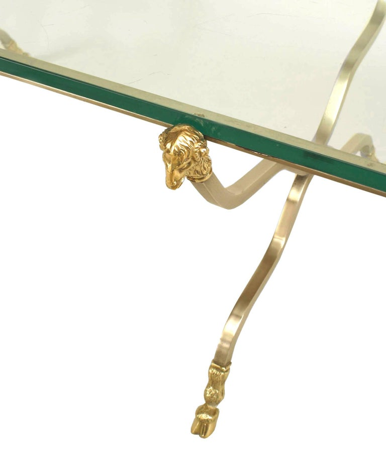 French Directoire-style (20th Century) rectangular coffee table with gilt steel six-legged base with brass ram head ornaments and feet and a glass top. (attributed to MAISON JANSEN)