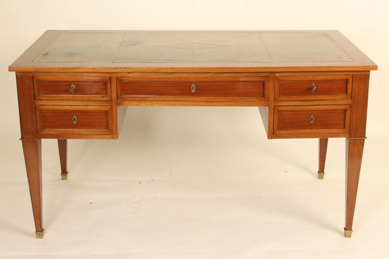 French Directoire style mahogany desk with a tooled leather top, circa 1910. Dimensions for knee hold opening, height 23.5