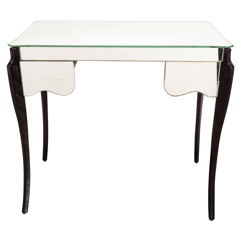 This elegant Art Deco French Directoire table was realized in France, circa 1940. It features stylized cabriolet style legs in ebonized walnut; a mirrored shield form top with chain bevelled detailing around the border with two drawers offering
