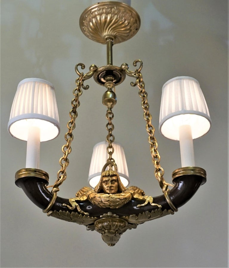 French 1910s three lights doré bronze and lacquer Empire style chandelier.