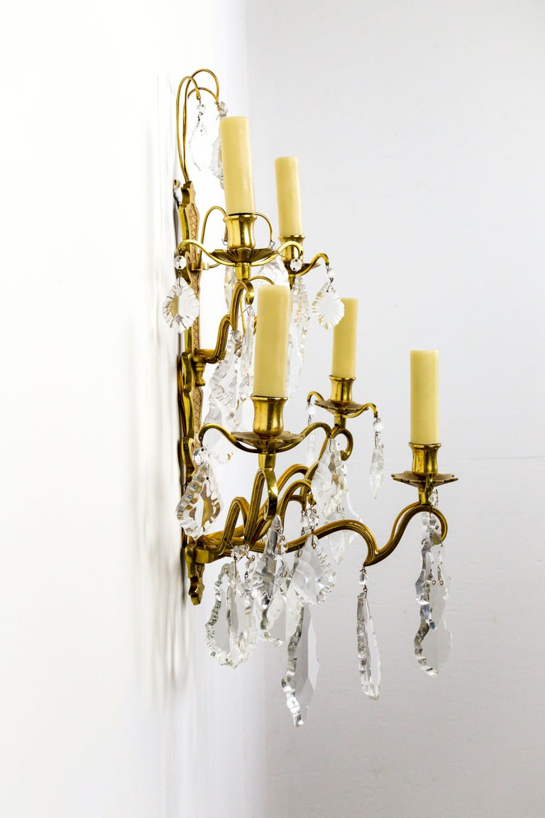French gilded bronze, double tier, five-arm, candelabra sconce in the Belle Époque style. With heavy, French pendalogue crystals, and polybeeswax candle covers, circa 1910. Newly rewired. Measures: 17