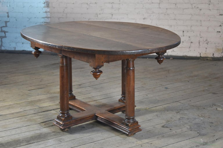 French Henry IV oval center, dining or breakfast table, early 17th century, of rare form and conceptual design, solid walnut with wonderful, deep patina. The oval top, consisting of three boards, over a rectangular frieze adorned with drop-finials
