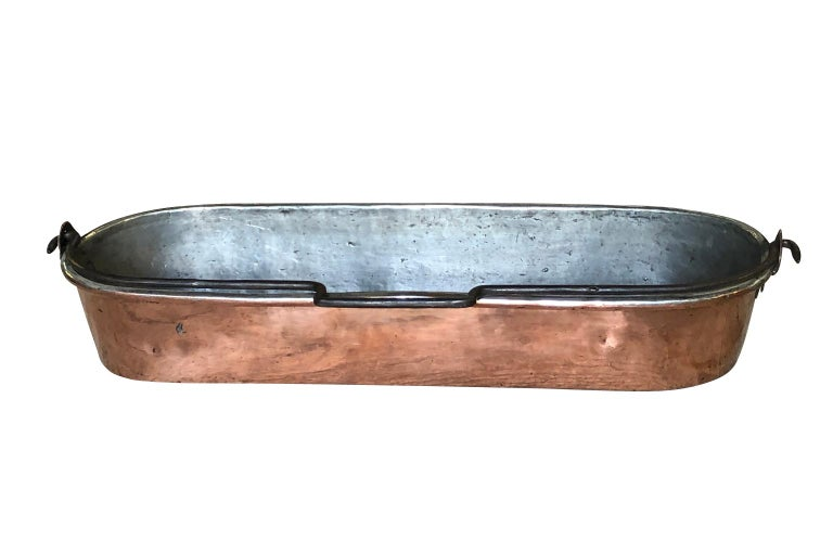 A very handsome early 19th century fish pan beautifully crafted from heavy gauge copper from the Provence region of France. A lovely accent piece for any kitchen, bathroom or table top.