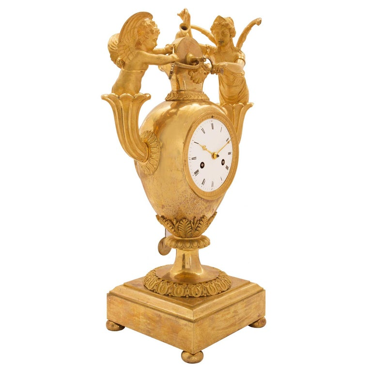 A remarkable French early 19th century First Empire ormolu clock, with the original silk threaded movement, dated 1809. Raised on a square moulded ormolu platform above bun supports. The pedestal base has a scalloped chasing below and a reeded one