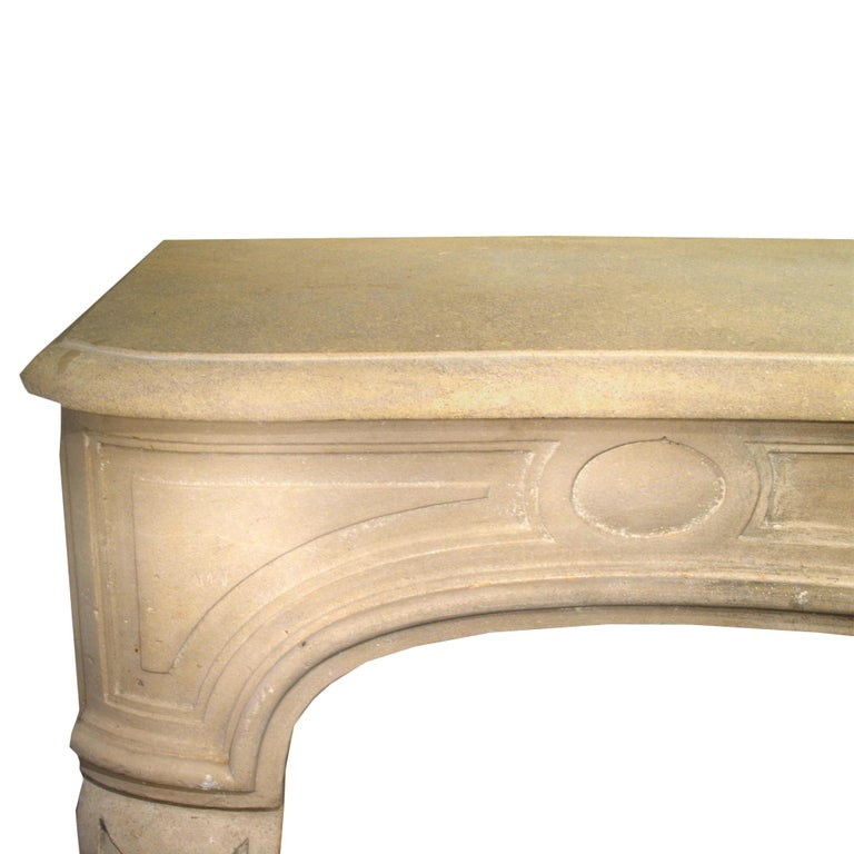 A stunning French early 19th century Louis XV style Limestone fireplace mantel. The volute fluted legs are supporting a swept frieze with a richly carved central shell amidst flowers flanked by Oeil de Boeuf carvings. The mantel has a serpentine