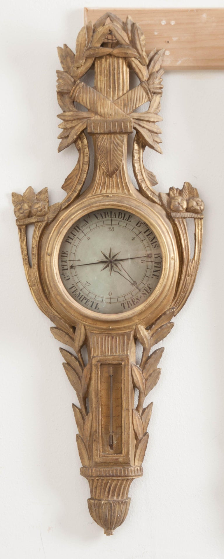 A gorgeous gold gilt barometer from the early part of the 19th century, France. This early scientific instrument was used to measure atmospheric pressure in order to better predict the weather. This antique piece has both a barometer as well as a