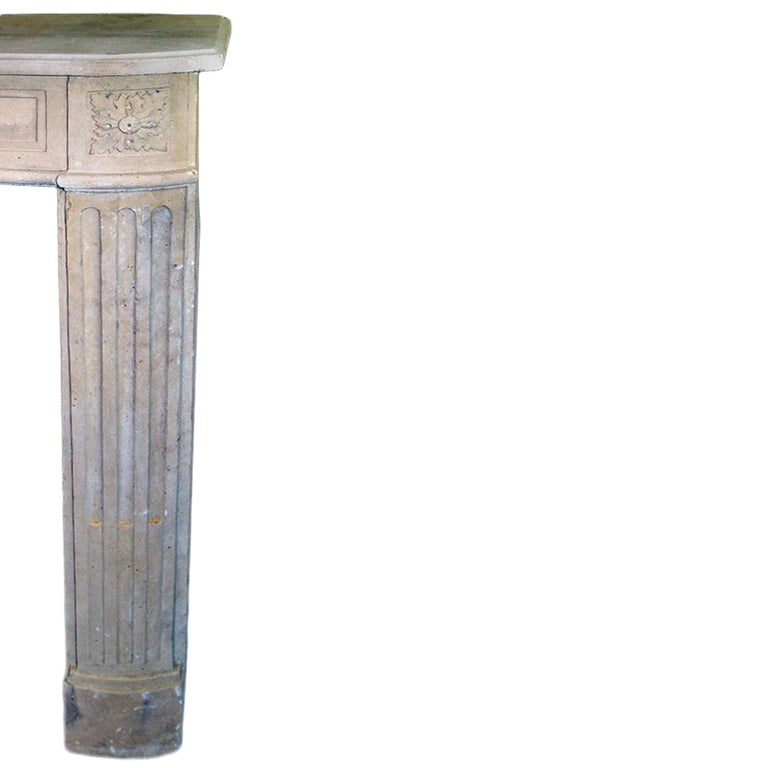A stunning French early 19th century Louis XVI style Limestone fireplace mantel. The volute fluted legs are topped by corner rosette blocks. The mantel has a straight rectangular top shelf.