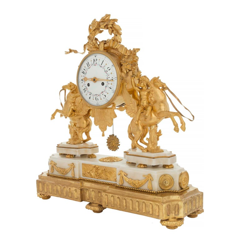 A stunning French early 19th century Louis XVI style ormolu, white Carrara marble and giltwood clock. The clock is raised by a fine giltwood base which mimics the most decorative shape of the clock. The base of the clock displays topie shaped feet,