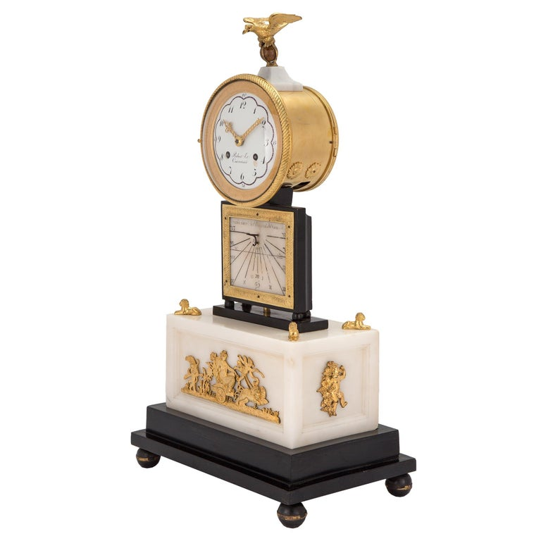 A very high quality and unique French early 19th century white Carrara marble and ormolu quarter strike clock with sundial signed Robert et Courvoisier. The clock is raised on an ebonized fruitwood support with ball feet. The rectangular white