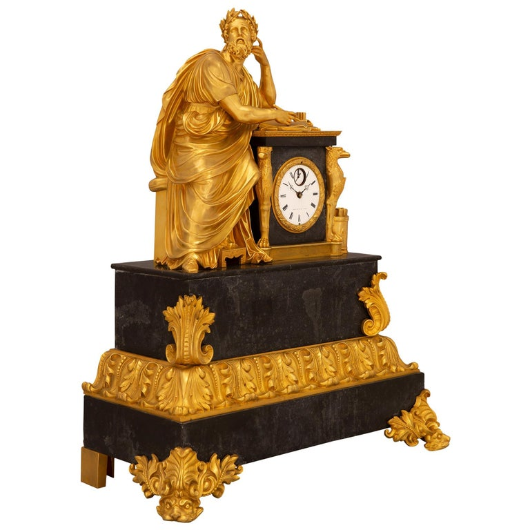 A stunning French early 19th century neo-classical style black Belgian marble and ormolu clock, stamped ARERA, circa 1830. The clock is raised by striking finely detailed ormolu supports with dolphins amidst beautiful scrolled movements and