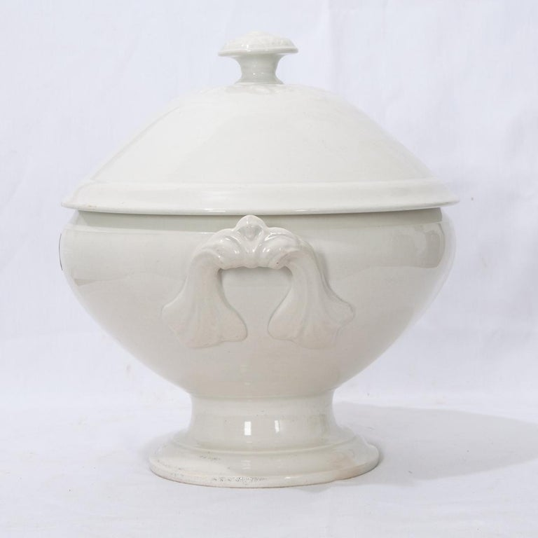 A gorgeous early 20th century, circa 1900, white ironstone tureen with fitted lid, from France. The stylish lid features a detailed knob handle. This tureen is perfect for serving soups, stews, or gumbos. Two handles are fashioned onto the sides.