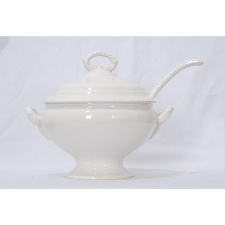 A gorgeous early French 20th century, circa 1900, white ironstone tureen with fitted lid and ladle. The stylish lid features a detailed pull handle. This white interior finish is clean, perfect for serving soups, stews, or gumbos. Two handles are