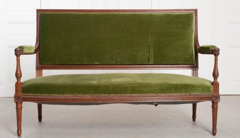 A fabulous green velvet upholstered Louis XVI style walnut settee, made in France, circa 1900. Magnificent carved details embellish nearly every square inch of the walnut frame. A carved, twisted ribbon motif runs the perimeter of the sofa's back,