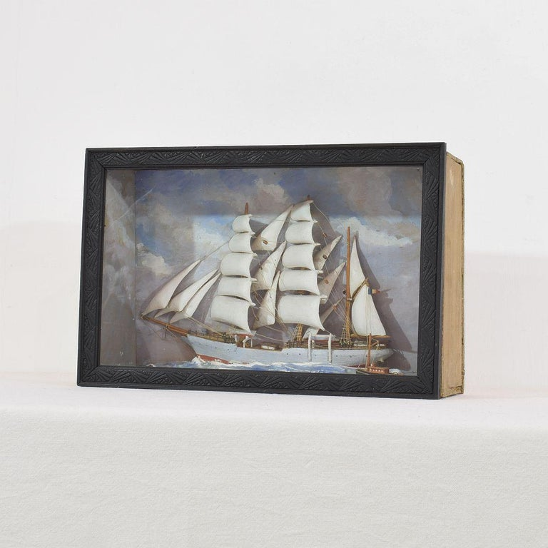Early 20 century diorama of a three masted ship in full sail in a choppy sea of white-capped white waves amidst blue skies with stormy clouds. In original framed glass shadow box.