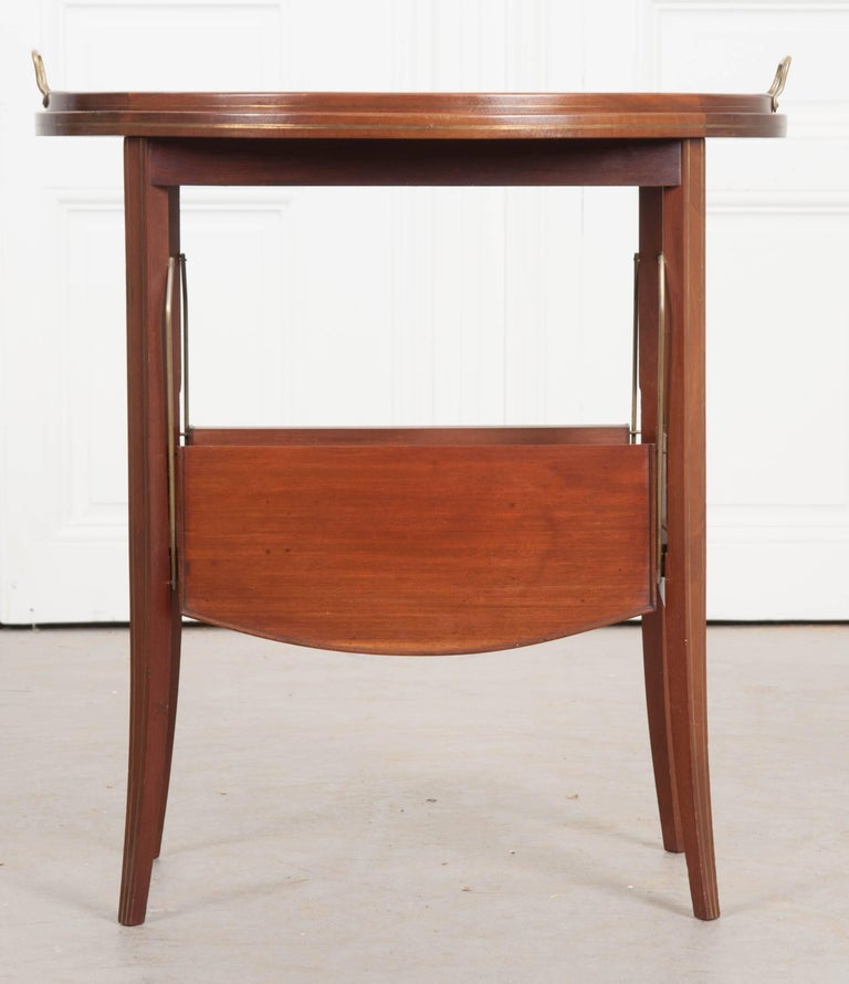 A wonderful mahogany tea table, circa 1910 from France. This early 20th century piece is in great antique condition, with the original tray top. This oval glass tray rests in the table's welled mahogany top and is complete with brass handles. The