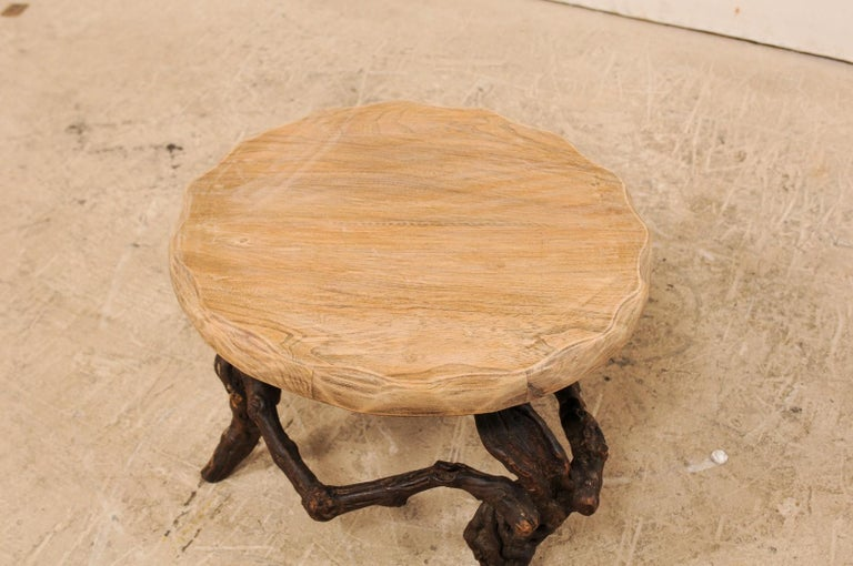 A French small sized coffee table with grapevine base from the early 20th century. This wonderfully informal antique table from France features a round-shaped wood slab top with carved scalloped edges, atop a natural grapevine base. This fabulous