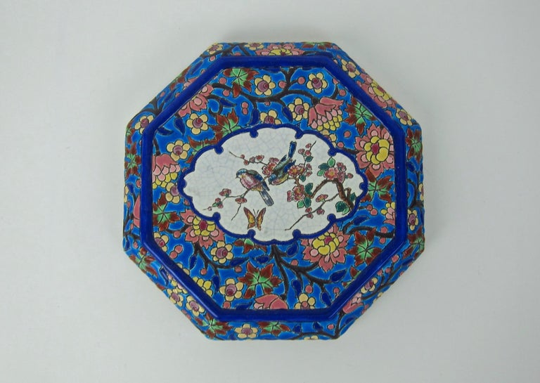 A colorful French faience trivet or stand from the Emaux de Longwy art pottery workshop in France. The vintage ceramic stand rests on four feet and is an octagonal shape designed for display and use on a tabletop.   The vivid enameled glaze in a