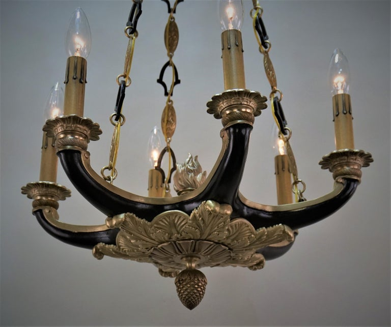 An elegant six-arm French bronze and black lacquer chandelier.