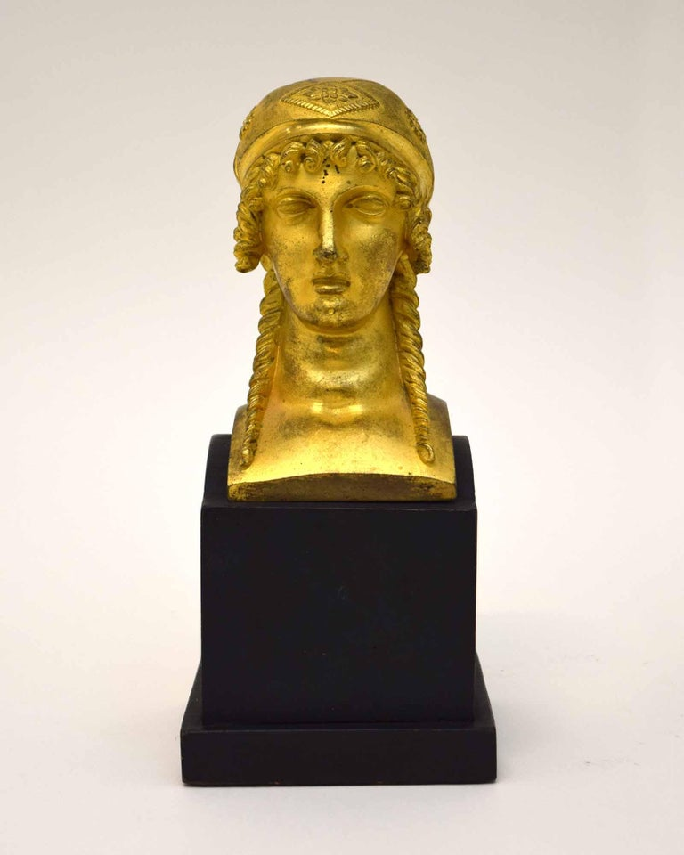 This Empire ormolu head of a woman was made as a furniture mount in France around 1810, and probably adorned a bed. In any case, closer to our own time, it was deemed worthy of mounting as a sculpture on a finely made base. Its neoclassical style,