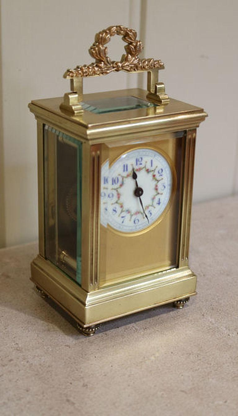A French Empire carriage clock, having a laurel leaf handle, reeded side columns and beaded round feet. The dial has a gilt dial mask and a hand decorated floral enamel dial with blue numerals. The 8 day movement has a cylinder platform.