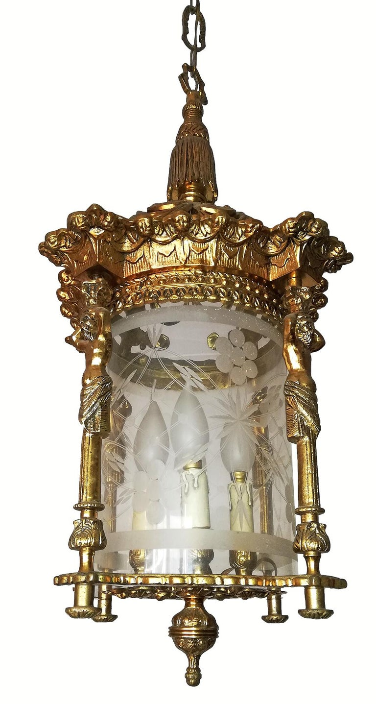 Beautiful pair of antique large French Empire cast bronze lanterns. Fire gilded solid heavy bronze and cut glass shade with four-light.