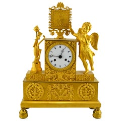 French Empire Clock Depicting a Standing Cupid and His Tools of Love