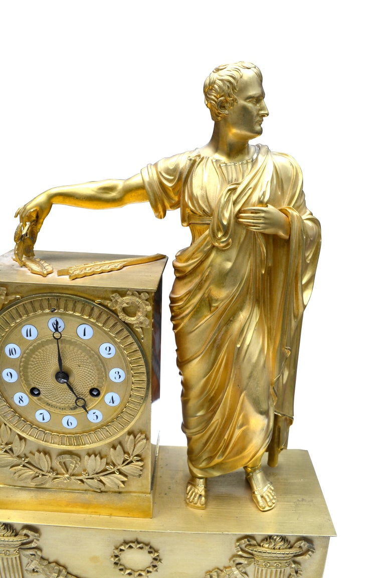 A finely chased and mercury gilded French Empire mantel (fireplace) clock showing a standing Napoleon dressed as Caesar holding leaves in his extended left hand. The clock plinth is decorated with wreath and laurel leaves; the lower rectangular base