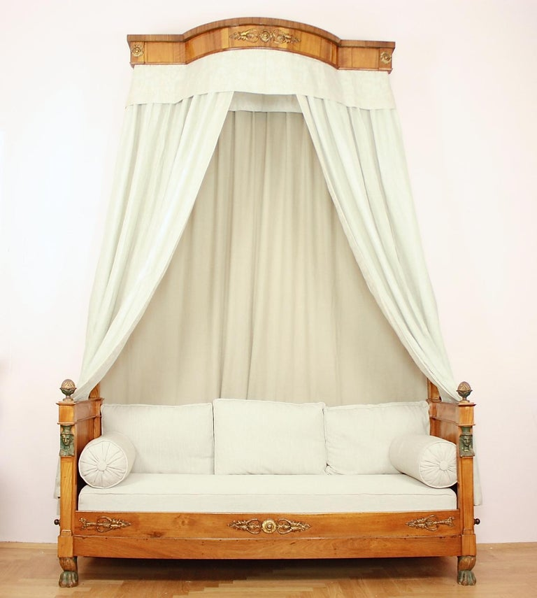A rare Empire daybed à 'l'ègyptien with a demilune canopy from circa 1815. Made of walnut with intricate carved decoration resembling gilt bronze mounts. The Egyptian heads and crocodile feet  were painted as if made of oxidized bronze. The gilded