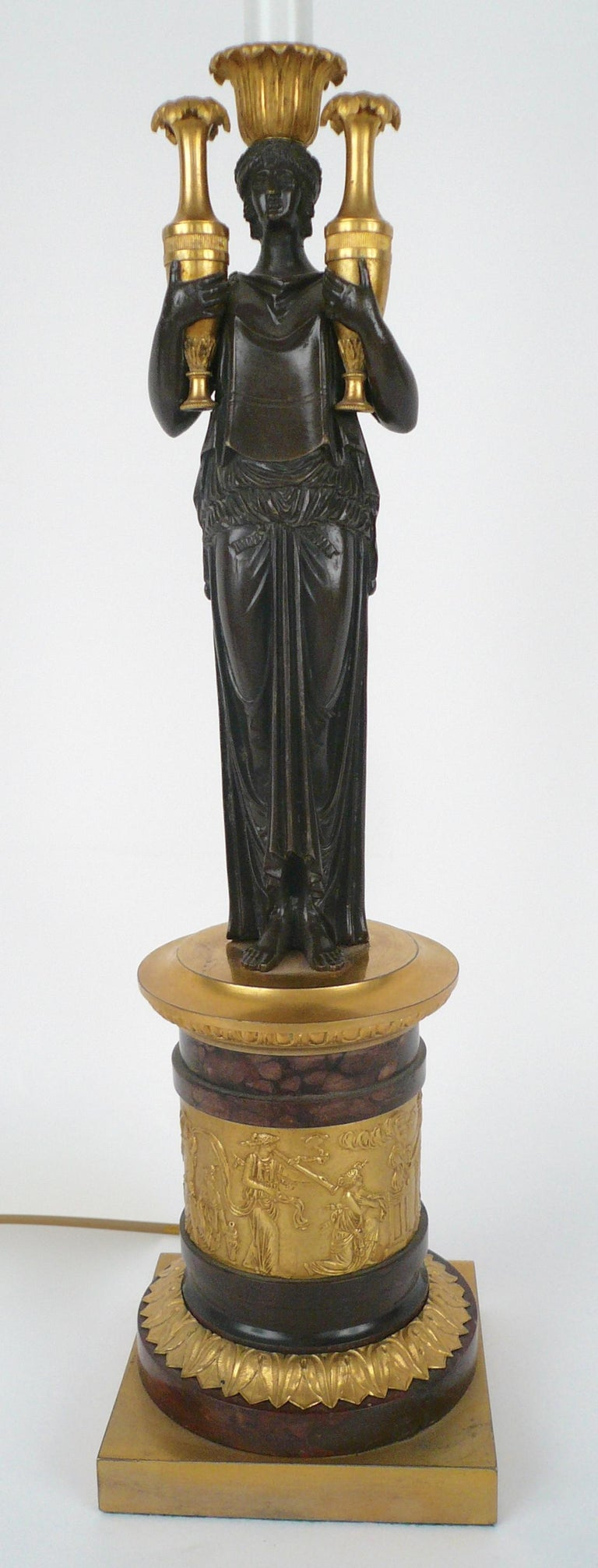This fine quality lamp base features a gilt classical frieze, and a patinated bronze figure of a classical maiden.
