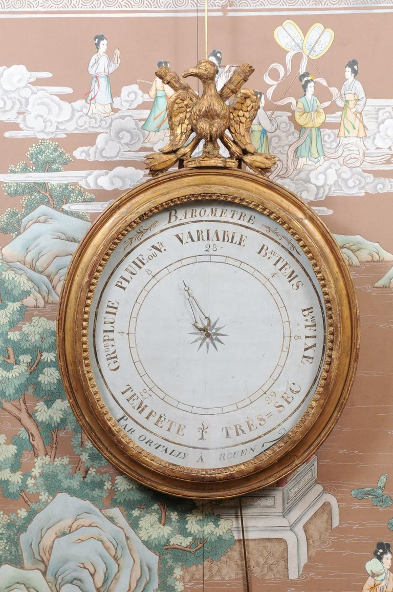 The early 19th century French large barometer with carved eagle crest on oval gilt-wood frame. The painted face with brass center dial and signed by maker