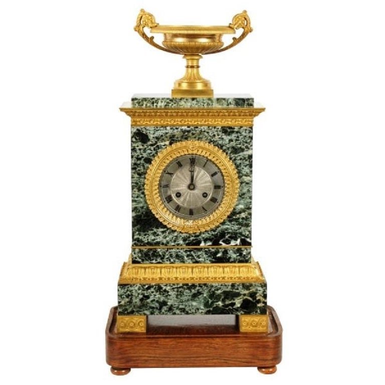 A 19th century French Empire design marble and ormolu table or mantel clock.  The clock has an eight day movement that strikes the hour and half hour on a bell and the pendulum is an early silk suspension.  The clock has a dark green with white