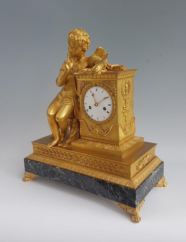 French Empire Ormolu and marble vert mantel clock of Cupid whispering. Wonderful original fire gilded mercury ormolu. The quality of the casting and chasing is superb, from the individual strands of cupids hair, to the tassle on the seat. Cupid sits
