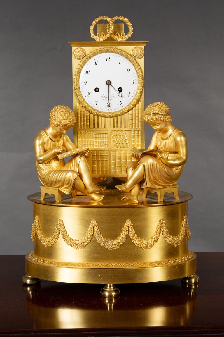 French Empire Ormolu mantel clock resting on four turned feet supporting an oval base with raised garland and zig-zag rope decoration. Two scholars are seated upon the base both studying books in front of the 'library' below the clock dial. The two