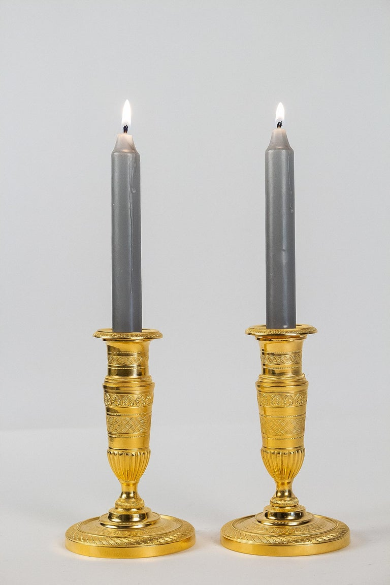 """French Empire period, pair of small gilt bronze candlesticks, circa 1805.  A rare and elegant pair of small gilt bronze candlesticks, called """"Ragots."""". Our candlesticks present a beautiful work of Fine shears, palmettes, interlacing, and geometric"""