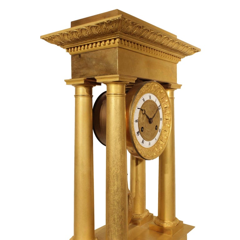 An exquisite French mid-19th century Empire style ormolu clock. The clock raised on a rectangular base with finely chased borders. Above four ormolu columns support the impressive top capitol with finely chased borders. Centered is the very