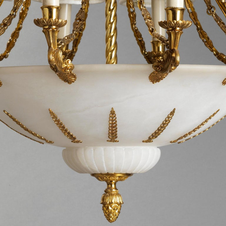 This exceptional 16-light gilt bronze and alabaster chandelier features best quality hand-chiseled details. Top crowns in characterized by rich vegetal decoration with acanthus leaves acroterion and alabaster . Below a tortile rod hold, together