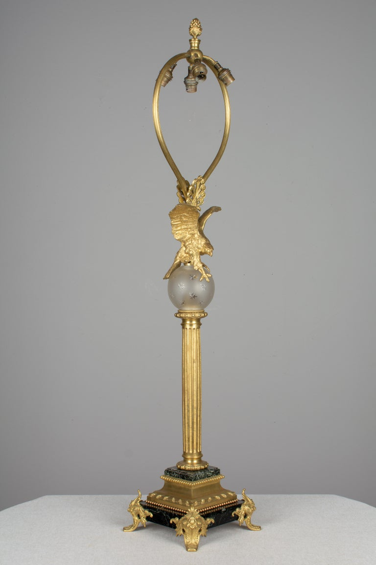 A French Empire style table lamp with cast bronze eagle perched on a frosted cut crystal globe decorated with stars. Tall fluted column on a bronze mounted marble base with bronze feet. Large reeded harp with four European sockets and pineapple