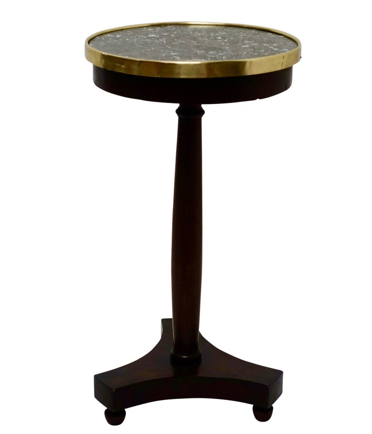 A unique Empire style mahogany side table or candle stand with an inset gray marble top and brass gallery, supported on a shaped column fixed to tripartite base sitting on acorn shape feet, France, circa 1840.