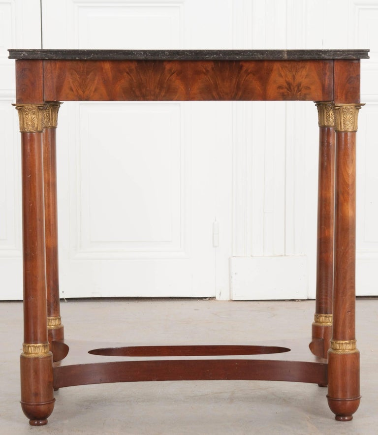 A fantastic mahogany Empire style table from France. Made at the beginning of the 20th century, this excellent little table has a beautiful black marble top that contains tiny fossilized creatures throughout. The marble is in terrific antique